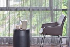 Ceramiczny kawowy ustawiający na górze stołu z ciemnego brązu rzemiennym krzesłem obraz stock