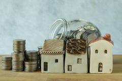Ceramiczny miniatura dom z stertą monety i monety w szkle j Zdjęcia Stock