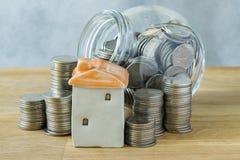 Ceramiczny miniatura dom z stertą monety i monety w szkle j Obrazy Stock