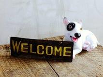 Ceramiczny pies z znakiem powitalnym na drewnianym tle zdjęcie royalty free