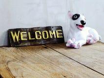 Ceramiczny pies z znakiem powitalnym na drewnianym tle obraz stock