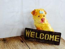 Ceramiczny pies z znakiem powitalnym na drewnianym tle zdjęcia stock