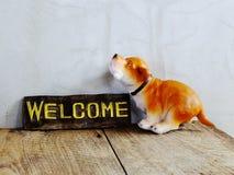 Ceramiczny pies z znakiem powitalnym na drewnianym tle obrazy stock