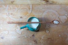 Ceramiczny pucharu miotacz ześrodkowywający na rocznika drewnianym tle z długą rzeźbiącą drewnianą łyżką ryż ryżu mleko balansowa zdjęcie stock