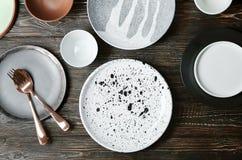 Ceramiczny tableware i cutlery na drewnianym tle Obrazy Stock