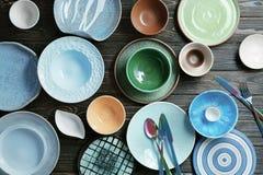 Ceramiczny tableware i cutlery na drewnianym tle, Zdjęcia Stock