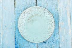 Ceramiczny talerz z wzorem na błękitnym starym drewnianym tle zdjęcia royalty free