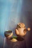Ceramiczny teapot, filiżanka czarna herbata z nowymi liśćmi i brown cukier na drewnianym stole z kopii przestrzenią, obraz royalty free