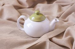 Ceramiczny teapot na tekstylnym tle zdjęcie stock