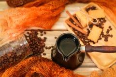 Ceramiczny turek, szalik, szklany słój, ciastka, cynamonowi kije i rozpraszać kawowe fasole na rocznika drewnianym stole, Odgórny zdjęcie royalty free