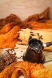 Ceramiczny turek, szalik, szklany słój, ciastka, cynamonowi kije i rozpraszać kawowe fasole na rocznika drewnianym stole, Odgórny obrazy royalty free