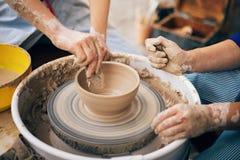 Ceramiczny warsztat R?ki doros?y i dziecko robi garncarstwu, pracuje z mokrym glinianym zbli?eniem Proces robi? pucharowi od glin obrazy royalty free