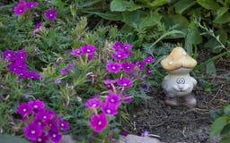 Ceramisch cijfer van een paddestoel onder purpere bloemen Stock Fotografie