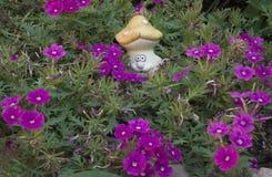 Ceramisch cijfer van een paddestoel onder purpere bloemen Royalty-vrije Stock Foto's