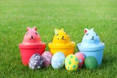 Ceramisch konijn drie met eieren op gras op Pasen-dag Stock Fotografie