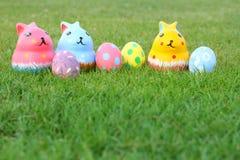 Ceramisch konijn met vier eieren op hoogste grasachtergrond in Pasen-dag Stock Foto's