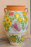 Ceramische die kruik met bloemenpatronen wordt verfraaid die clusters schenken van royalty-vrije stock afbeeldingen