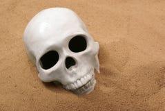 Ceramische menselijke schedel in zand Stock Foto's