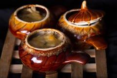 Ceramische potten met het gebakken vlees en de kaas op een houten steun Royalty-vrije Stock Afbeeldingen