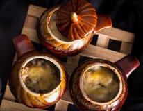 Ceramische potten met het gebakken vlees en de kaas op een houten steun Royalty-vrije Stock Fotografie