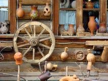 Ceramische productentribune dichtbij het venster van een oud blokhuis stock afbeelding