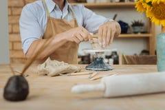 Ceramist, der Keramik Jigger steht nahen Vase mit Sonnenblumen verwendet lizenzfreie stockbilder