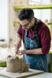 Ceramist Dressed in an Apron Sculpting Statue from Raw Clay in Bright Ceramic Workshop. Royalty Free Stock Photography