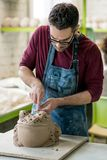 Ceramist Dressed in an Apron Sculpting Statue from Raw Clay in Bright Ceramic Workshop. Royalty Free Stock Image