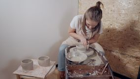 Ceramist master woman is making tableware using traditional potter`s wheel. Female potter is working with potter`s wheel, modeling handmade clay bowls. She is stock video