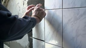 Ceramist puts tile on the wall stock video