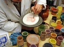 Ceramist som målar en religiös tegelplatta i dess krukmakeriseminarium, Triana, Sevilla, Spanien royaltyfri fotografi