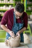 Ceramist vestido em um avental que esculpe a estátua da argila crua na oficina cerâmica brilhante Fotos de Stock Royalty Free