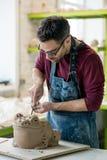 Ceramist vestido em um avental que esculpe a estátua da argila crua na oficina cerâmica brilhante Fotografia de Stock Royalty Free