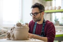 Ceramist vestido em um avental que esculpe a estátua da argila crua na oficina cerâmica brilhante Foto de Stock
