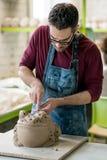 Ceramist vestido em um avental que esculpe a estátua da argila crua na oficina cerâmica brilhante Imagem de Stock Royalty Free