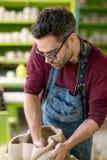 Ceramist vestido em um avental que esculpe a estátua da argila crua na oficina cerâmica brilhante Imagens de Stock