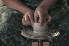 Ceramist with wet hands forms a jug of clay on a rotating potter`s wheel Royalty Free Stock Image