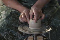 Ceramisten med våta händer bildar en tillbringare av lera på ett roterande hjul för keramiker` s Royaltyfri Bild