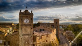 Cerasa Ancient Tower of the medieval village. Cerasa di San Costanzo, ancient medieval tower with clock at sunset. Drone picture. Cerasa is a fraction belonging royalty free stock photo