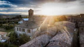 Cerasa Ancient Tower of the old village at the sunset. Cerasa di San Costanzo, ancient medieval tower with clock at sunset. Drone picture. Cerasa is a fraction royalty free stock photo