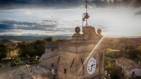 Cerasa Ancient Tower of the old village at the sunset. Cerasa di San Costanzo, ancient medieval tower with clock at sunset. Drone picture. Cerasa is a fraction stock photo