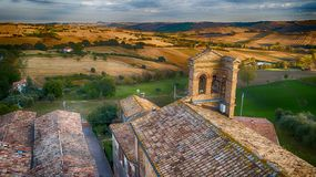 Cerasa di San Costanzo, Marche, Italy. Drone wiew. Aerial view of the roofs and the church overlooking a beautiful view of the countryside at sunset royalty free stock images