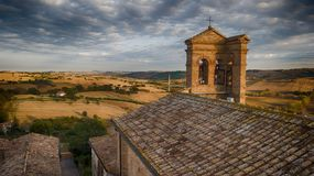 Cerasa di San Costanzo, Marche, Italy. Drone wiew. Aerial view of the roofs and the church overlooking a beautiful view of the countryside at sunset royalty free stock photos