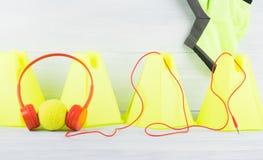 Cerca amarilla del cono en la camiseta gris del fondo y del deporte, detrás de la pelota de tenis que está llevando los auricular Imagen de archivo libre de regalías