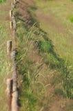 A cerca ao longo da estrada de terra Cerca com cargos de madeira Uma estrada secundária País Fotos de Stock