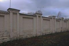 Cerca branca velha do tijolo sob um céu nebuloso fotografia de stock