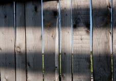 Cerca cinzenta de madeira velha do close-up feita das placas com teste padrão de tiras solares nelas fotos de stock royalty free