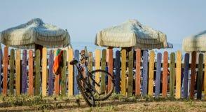 Cerca colorida na praia com guarda-chuvas retros e bicicleta Estilo da cor de tom do vintage Foto de Stock