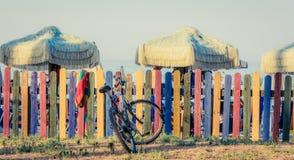 Cerca colorida na praia com guarda-chuvas retros e bicicleta Estilo da cor de tom do vintage Fotografia de Stock