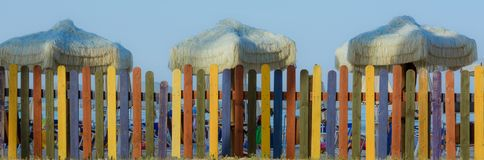 Cerca colorida na praia com guarda-chuvas retros Estilo da cor de tom do vintage Imagens de Stock Royalty Free